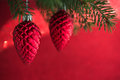 Red christmas ornaments cones on the xmas tree on red background.