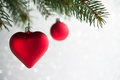 Red christmas ornaments heart and ball on the xmas tree on glitter bokeh background. Royalty Free Stock Photo