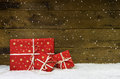 Red christmas presents on wooden background with snowflakes.