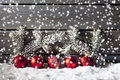 Red christmas spheres on pile of snow against wooden wall Royalty Free Stock Photo