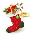 Red christmas stocking with gifts greetings from santa claus santa claus gift nicholas gift in boots filled nicholas boots Stock Photography