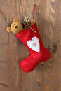 Red christmas stocking on an old door filled with a handmade teddy bear and gifts hanging by a rusty nail in Royalty Free Stock Photo