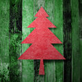 Red Christmas tree on green wooden texture Royalty Free Stock Image