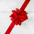 Red christmas or valentines bow romantic vivid placed diagonally across white painted boards as a festive background for your Royalty Free Stock Images