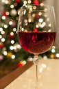 Red christmas wine a glass of with glittering tree lights in the background Royalty Free Stock Images