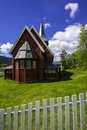 Red church on green yard a stave in a small town of norway with a and a fence Royalty Free Stock Photos