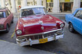 Red classic cuban car diagonal parking in street parked havana cuba Stock Photography