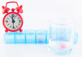 Red clock and pink tablet in prescription glass show medicine time background Stock Photos