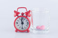 Red clock and pink tablet in prescription glass show medicine time concept Stock Photos