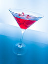 Red cocktail drink with ice cubes on blue light tint background, fun and dance disco Royalty Free Stock Photo