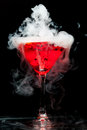 Red cocktail with ice vapor on black background Stock Photo