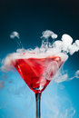 Red cocktail with ice vapor blue background Royalty Free Stock Photos