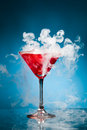 Red cocktail with ice vapor blue background Royalty Free Stock Images
