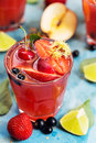 Red cocktail with slices of apple, strawberry and lime Royalty Free Stock Photo
