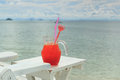 Red cocktail on white table set over ocean Stock Photography