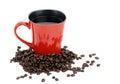Red coffee mug with whole dark roast beans around it Stock Image