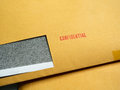 Red `Confidential` word printed on brown vintage envelope. Business confidential concep Royalty Free Stock Photo
