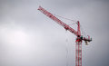 Red construction crane tower and an industrial building site on an overcast cloudy day Stock Photo
