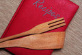 Red cookbook book of recipes with wooden cutlery Stock Photos