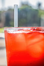 Red cordial drink in a cup with ice and straw focus is generally on the straw Royalty Free Stock Photos