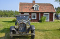 Red cottage wooden in sweden and a old car in front Stock Photography