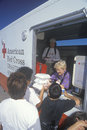 A Red Cross worker handing out meals Stock Images