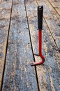 Red crowbar pulling a rusty nail to demonstrate the concept of leverage Royalty Free Stock Photo