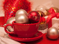 stock image of  A red cup, bright red, silver and golden fir balls, festive caps and a little gift box