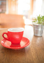 Red cup of coffee and green plant bucket on wooden table Royalty Free Stock Photo