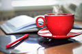 Red cup of hot coffee, notepad and pencil on the desktop in the office. Royalty Free Stock Photo