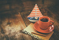 Red cup of tea and letter paper next to vintage decorative boat on wooden old table. retro filtered image Royalty Free Stock Photo