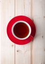 Red cup with tea on saucer Royalty Free Stock Photo