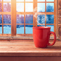 Red cup on wooden table over window with winter nature view. Winter and Christmas holiday concept. Cup mock up template for logo s Royalty Free Stock Photo