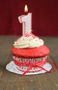 Red cupcake velvet with a number one candle on it Royalty Free Stock Images