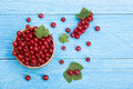Red currant berries in a wooden bowl with leaf on the blue wooden background with copy space for your text. Top view Royalty Free Stock Photo