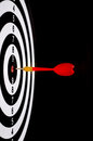 Red dart arrow hitting in the target center of dartboard with black background Royalty Free Stock Photography