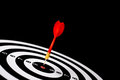 Red dart arrow hitting in the target center of dartboard with black background Stock Image