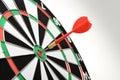 Red dart hitting target center on white background Stock Photos