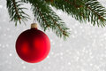 Red decorative ball on the xmas tree on glitter bokeh background. Merry christmas card. Royalty Free Stock Photo