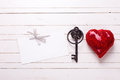 Red decorative  heart, empty tag  and key on  white  wooden back Royalty Free Stock Photo