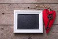 Red decorative  heart, key  and empty blackboard on aged wooden Royalty Free Stock Photo