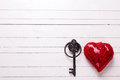 Red decorative  heart and key on  white  wooden background. Royalty Free Stock Photo
