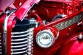 Red devil buick special retro street rod antique car front end detail headlight and chrome grille with open hood panel over high Stock Photos