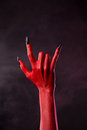 Red devil hand showing heavy metal gesture studio shot on smoky background Stock Photos