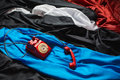 Red dial phone on a crumpled tissue, colored fabrics, raw material, red, black, blue, white cloth, Royalty Free Stock Photo