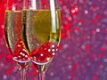 Red dice dropping in the champagne flutes on red and violet tint light bokeh background Royalty Free Stock Photo