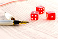 Red dice and golden pen on financial newspaper Royalty Free Stock Image