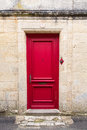 Red door view of a beautiful and clean on a white stone brick wall Royalty Free Stock Images