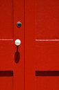 Red door white doorknob with in sunlight with shadow Royalty Free Stock Image