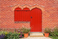 Red door and windows on red brick wall Royalty Free Stock Photo